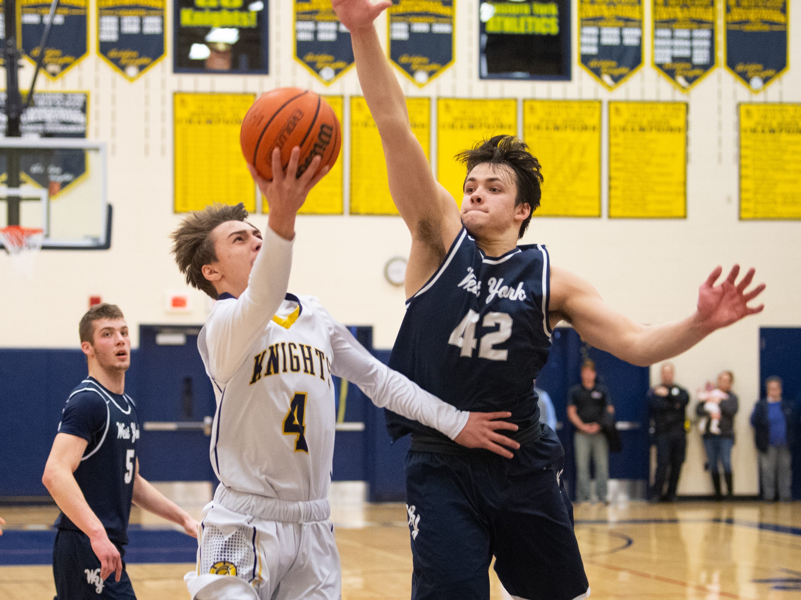 Gabe Mummert (42) looks to block Trevor Seitz (4) during the YAIAA boys' basketball game between Eastern York and West York, Friday, January 25, 2019 at Eastern York High School. The Golden Knights defeated the Bulldogs 59 to 55.