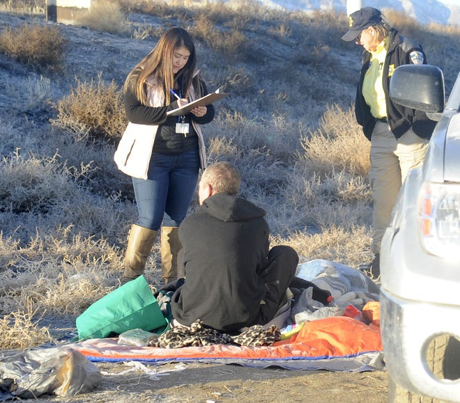 Case Manager Lucrecia Salguero talks with a homeless man who slept on the ground outside a dilapidated vehicle.