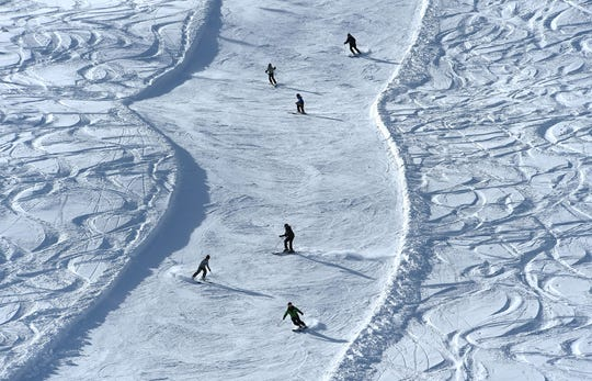 Skiers make their way down a groomed run during opening day for the Sky Tavern Jr. Ski Program near Reno on Jan. 26, 2019.