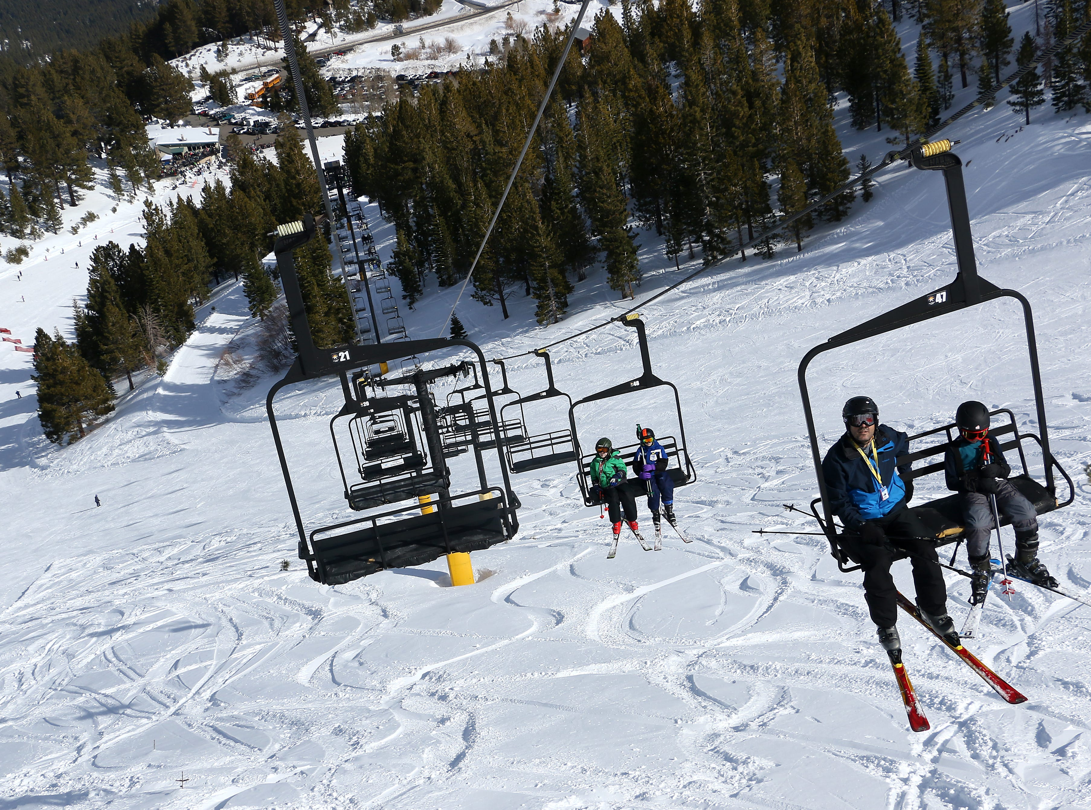 Skiers ride the lift up to the top during opening day for the Sky Tavern Jr. Ski Program near Reno on Jan. 26, 2019.