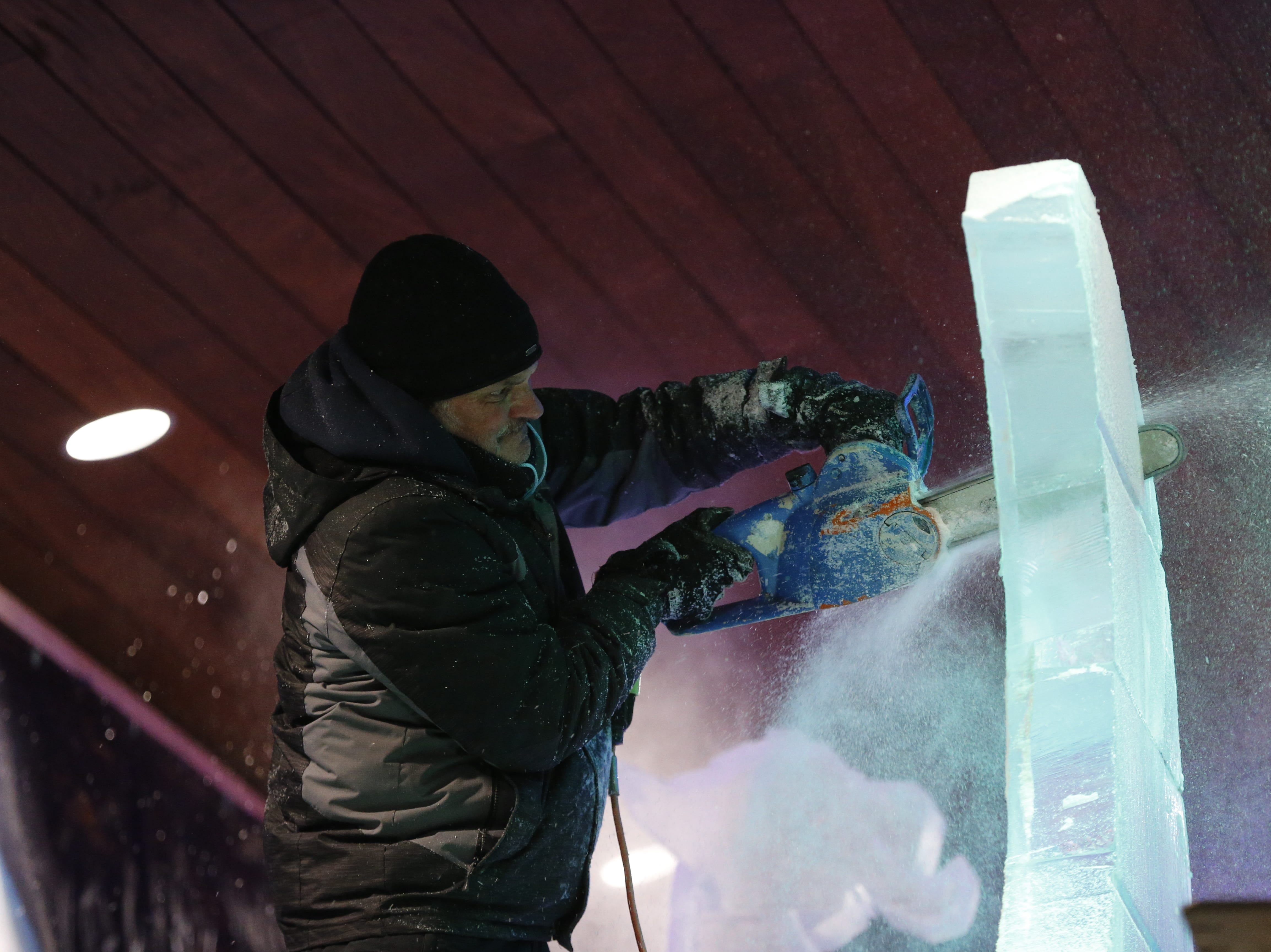 """Snow flies as a chainsaw makes quick work of a block of ice during the Meltdown Winter Ice Festival's """"Big Reveal"""" event on Friday."""