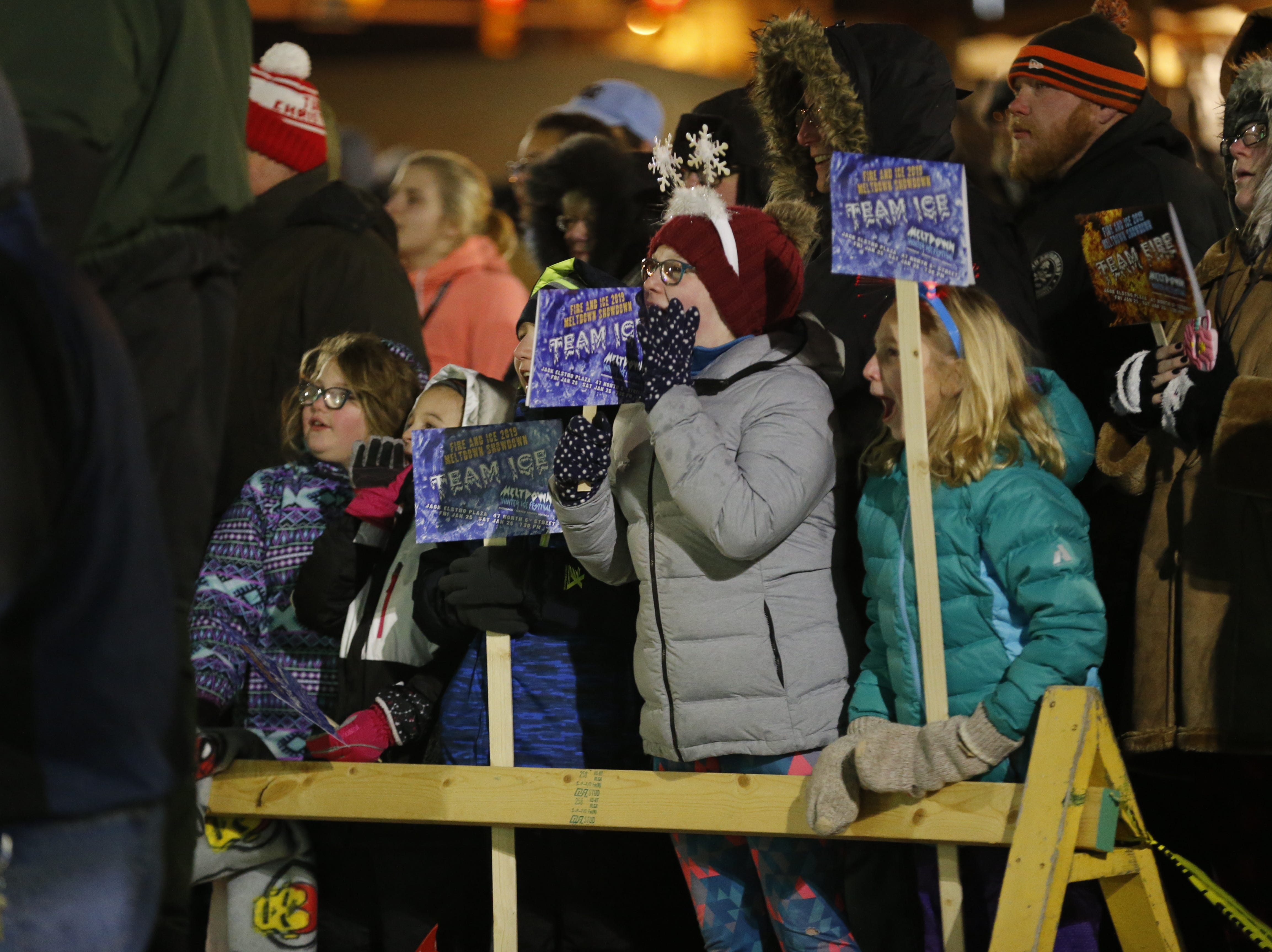 """Young """"blockheads"""" cheer for their favorite ice carver during Richmond's Meltdown Winter Ice Festival on Friday night at Jack Elstro Plaza."""