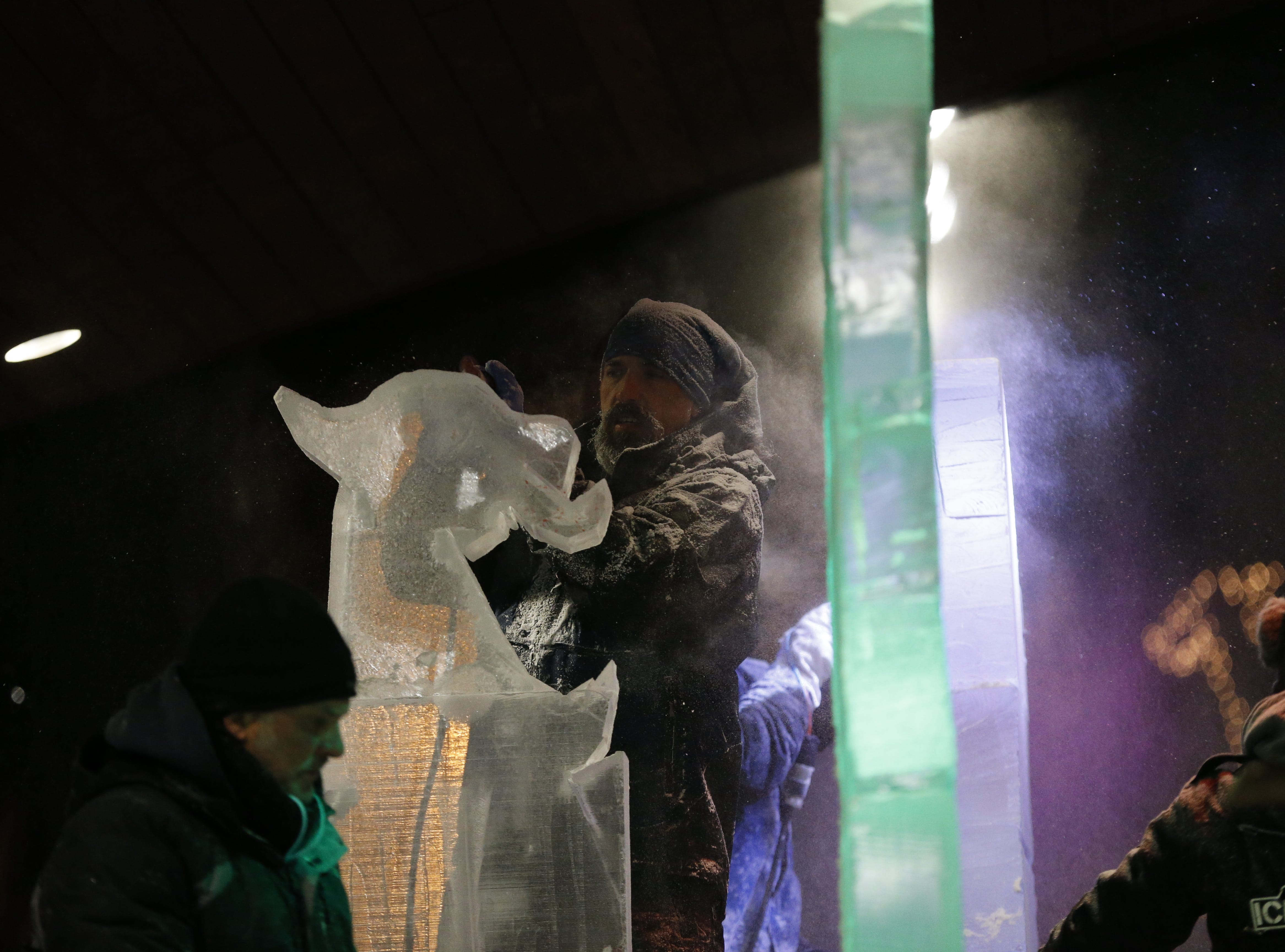 """An ice carver goes to work on one piece of what turned out to be a phoenix sculpture during the Meltdown Winter Ice Festival's """"Big Reveal"""" event on Friday."""