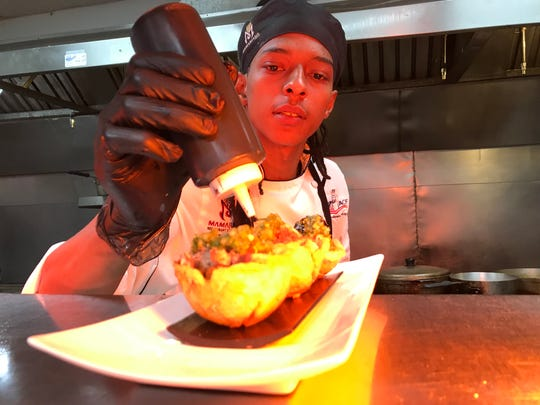 Angel Lopez puts the finishing touches on a dish at MamaJuana Restaurant and Lounge in Rochester.