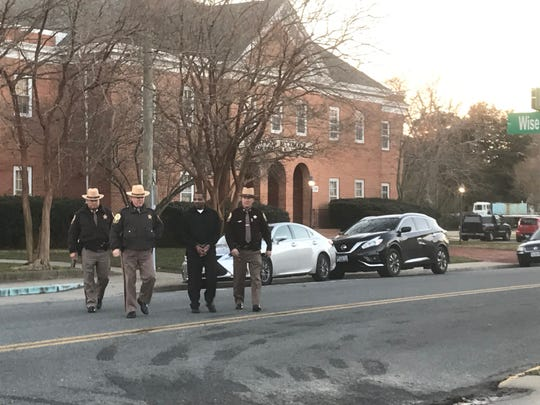 Evron Terrell Strand, in black clothing, is escorted from the courthouse back to Accomack County Jail by three Accomack County Sheriff's Office officers on Friday, Jan. 25, 2019 after he was convicted of seven charges, including attempted capital murder for hire.