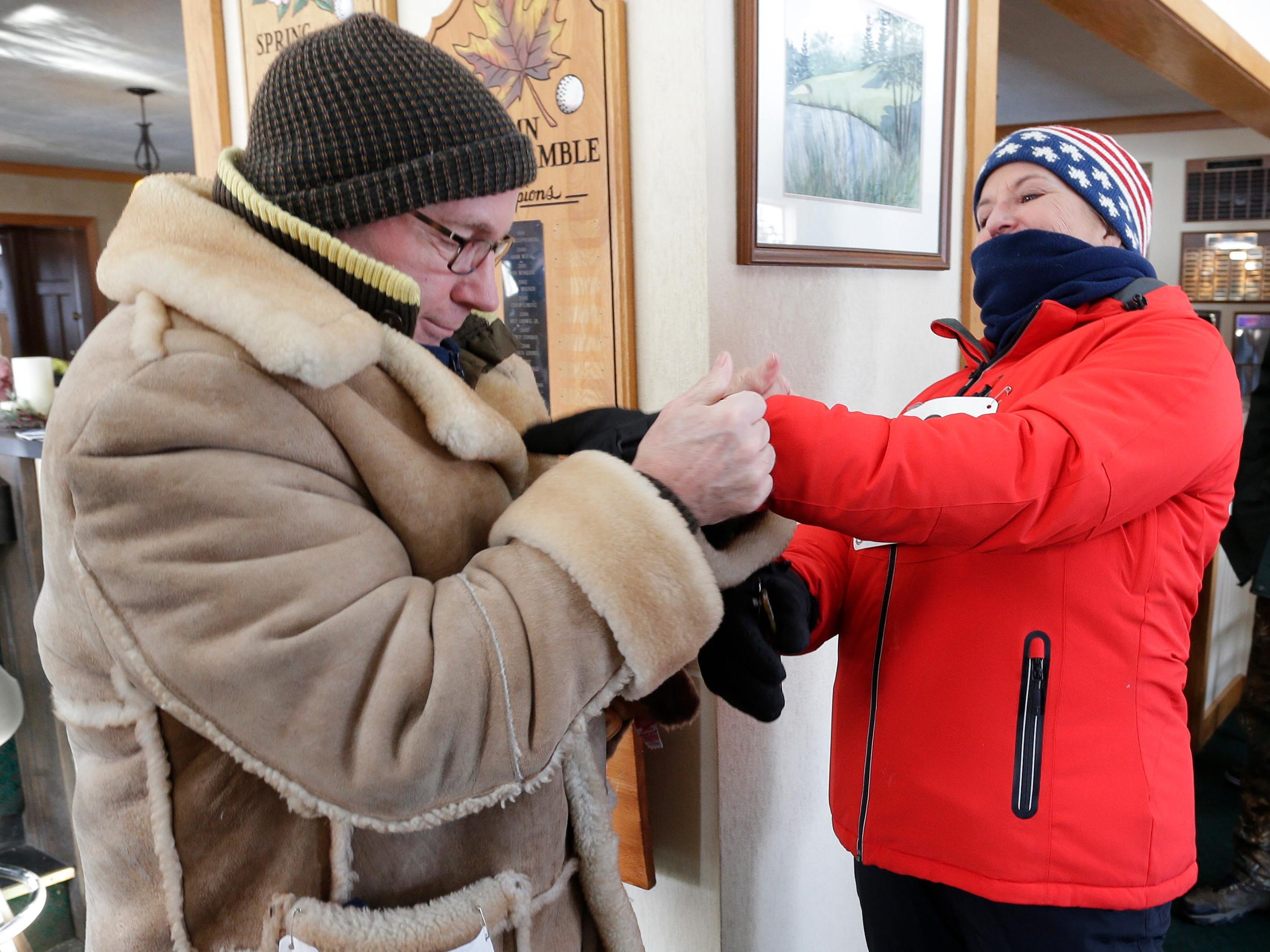 Thomas Liebl, left, helps his wife Lisa put her mittens on before the Schneelauf Run, Saturday, January 26, 2019, in Elkhart Lake, Wis.