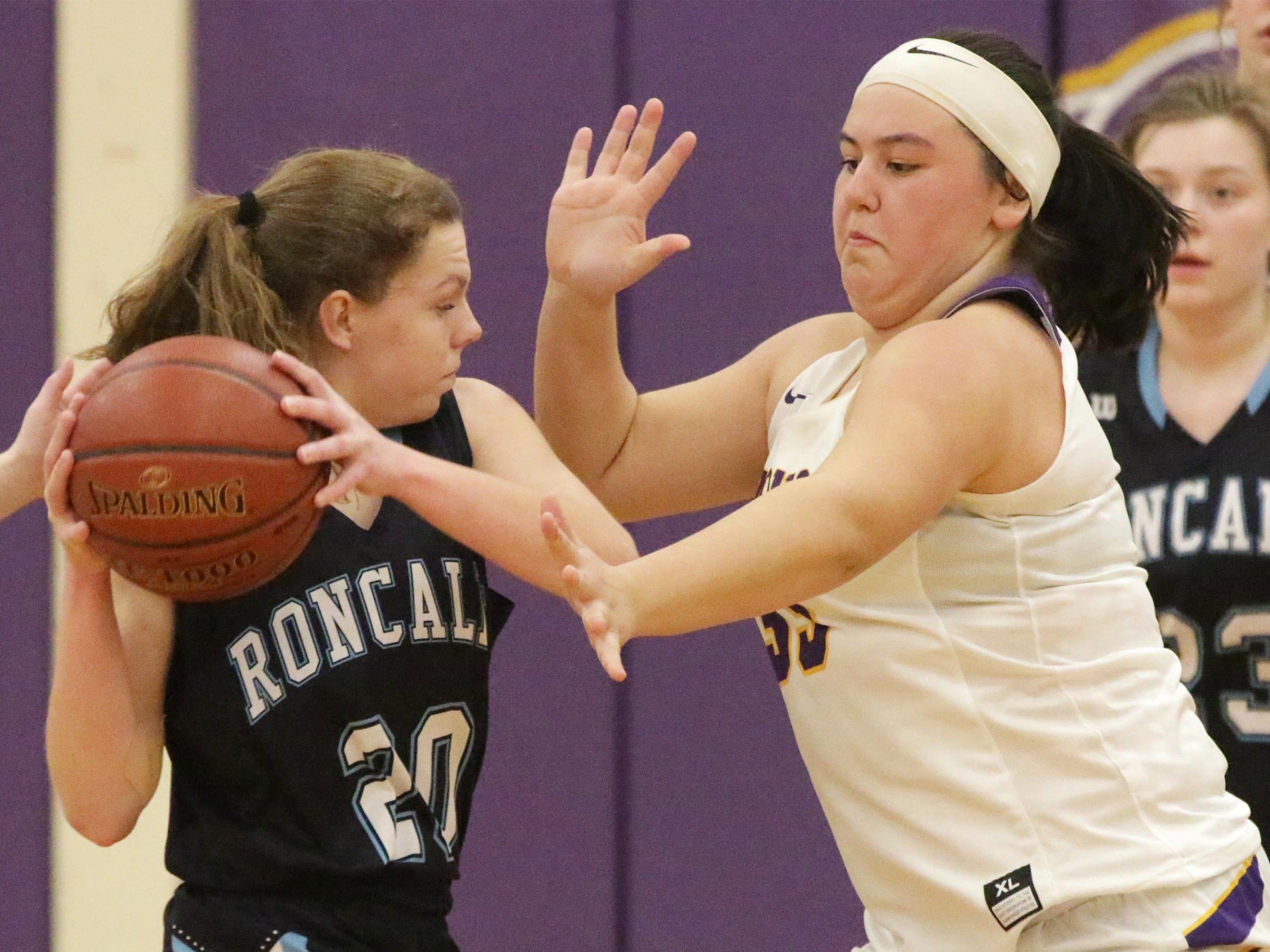 Roncalli's Gonna Schramm (20) looks to pass the ball by Sheboygan Falls' Jordyn Girdaukas (35), Friday, January 25, 2019, in Sheboygan Falls, Wis.