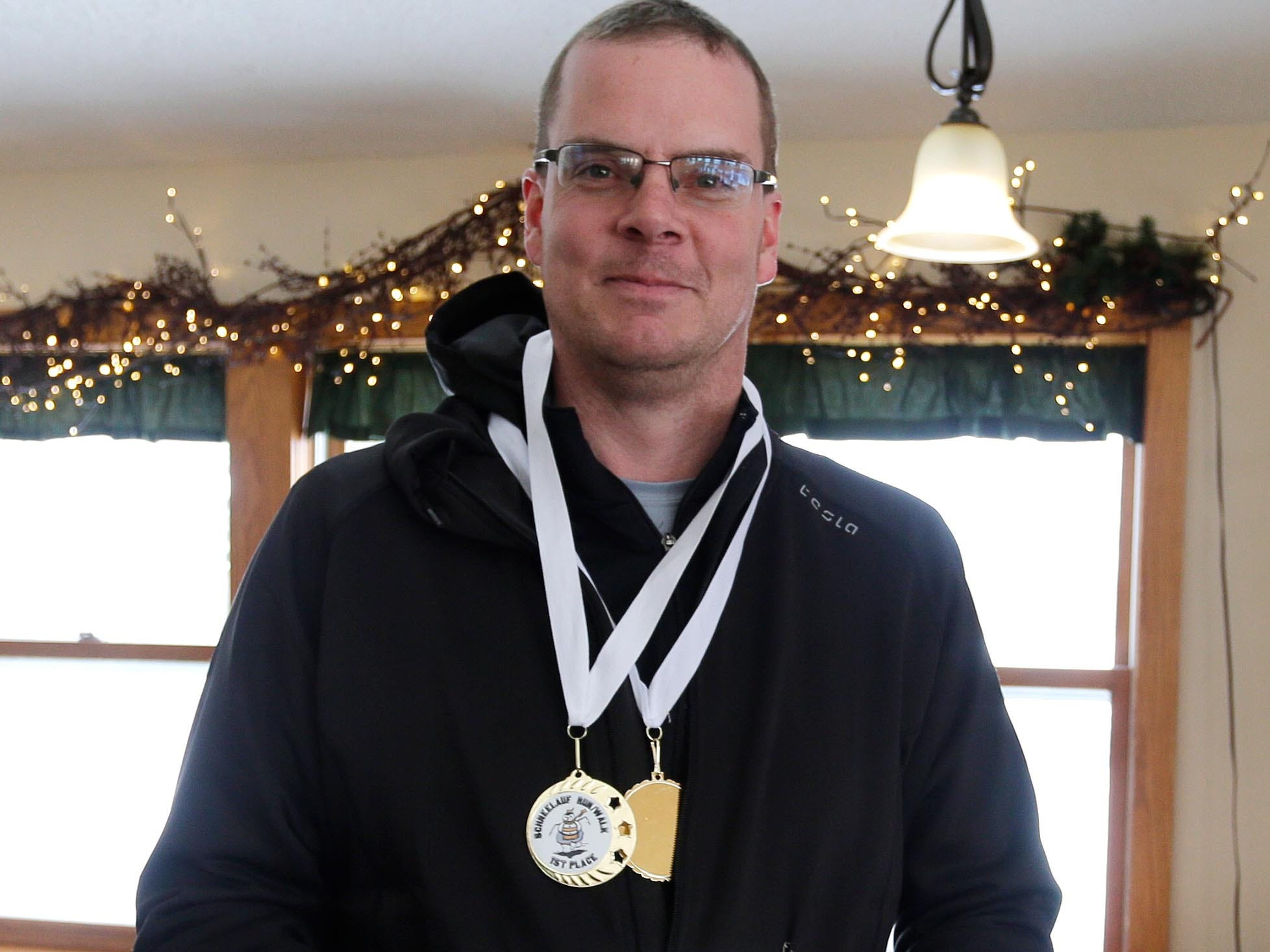 Mark Burgard (9) of Manitowoc, Wis. poses with his medals following Schneelauf Run, Saturday, January 26, 2019, in Elkhart Lake, Wis. Burgard took first place with a time of 13:59 for the two-mile event.