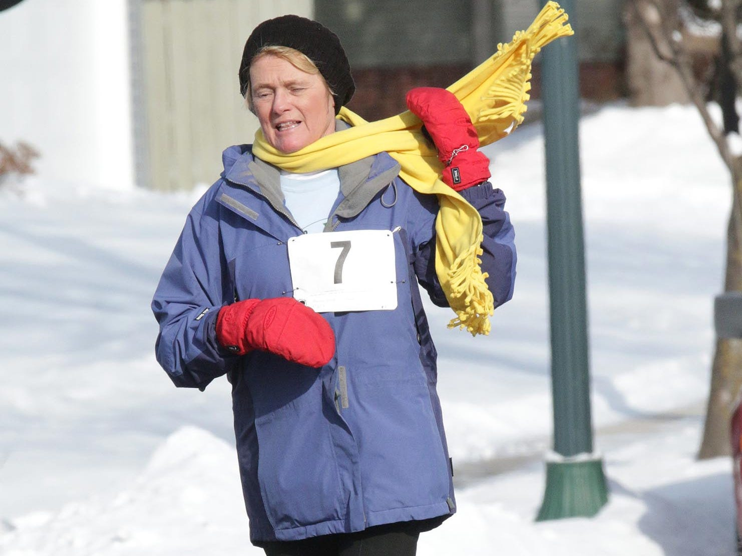 Therese Wilk (7) of Elkhart Lake whips her scarf around her neck while running in the 2-mile Schneelauf Run, Saturday, January 26, 2019, in Elkhart Lake, Wis. The event is part of Schnee Days in Elkhart Lake. Wilk's time in the 60 and over class was 27:43