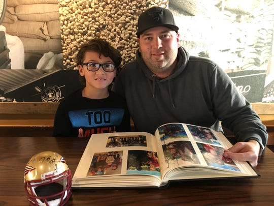 Payton and Michael Ramsey look over a photo album that they keep with photos of the celebrities they've met.