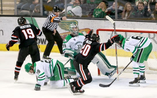 St, Cloud State's Sam Hentges (19) and Nolan Walker (20) react to Patrick Newell's game-winner in the third Friday in Grand Forks.