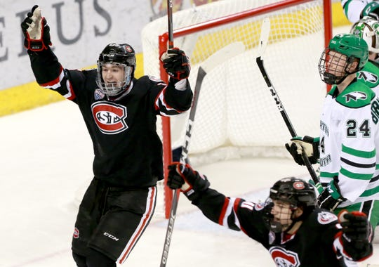 St. Cloud State's Nick Perbix and Jon Lizotte celebrate the Huskies' first goal in the second period against North Dakota in Friday's NCHC game at the Ralph Engelstad Arena. UND's Jacob Bernard-Docker looks on.