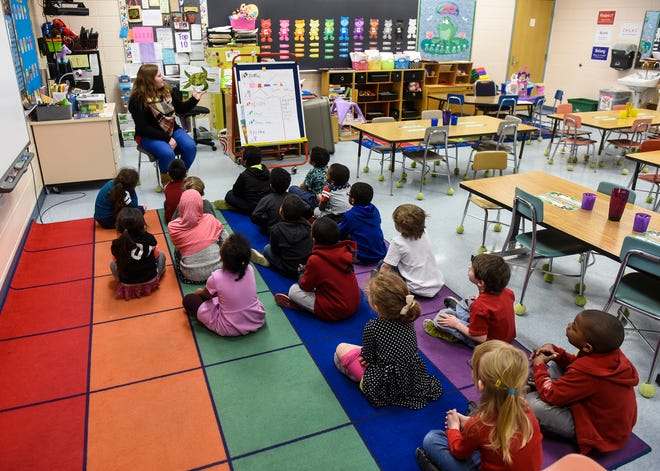Kindergartners gather around Samantha Backer as she reads a book Friday, Jan. 25, at Talahi Community School in St. Cloud. Backer is a permanent substitute teacher, who fills in whenever Teachers On Call is unable to find a sub for Talahi.
