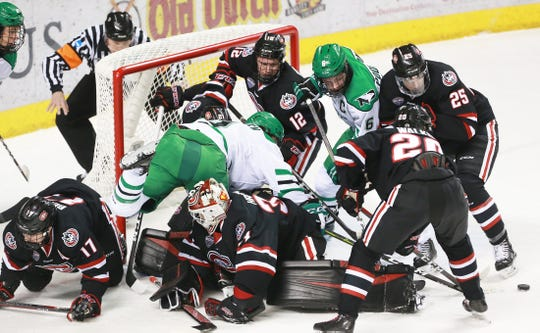 A scrum of UND and St. Cloud State players look for the puck in the Huskies' zone in the first period.