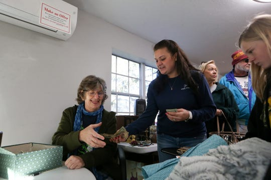 Hailey Peters, center, hands $50 to Rita Leblanc, a volunteer at St. Marks Wildlife Refuge and the cashier at a yard sale held at Unity Eastside Church to benefit federal workers furloughed during the government shutdown Saturday, Jan. 26, 2019. Peters bought a blanket, place mats and a rolling office chair for $42 and told Leblanc to keep the change.
