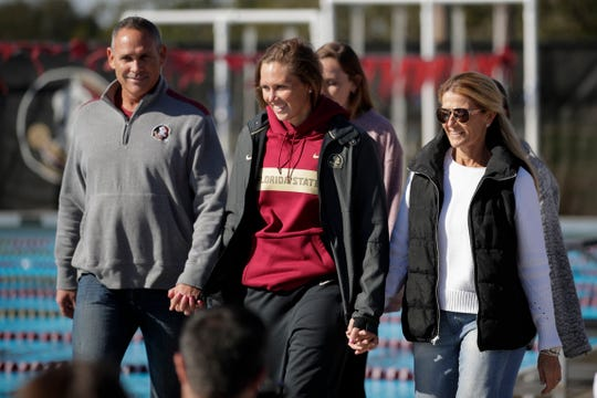 Florida State University's McKenna Keith walks across the pool deck with her parents Michael and Ginger Keith on Senior Day at the Morcom Aquatics Center on Saturday, Jan. 26, 2019. The meet marked Keith's first return to the pool after defeating Hodgkin's lymphoma.