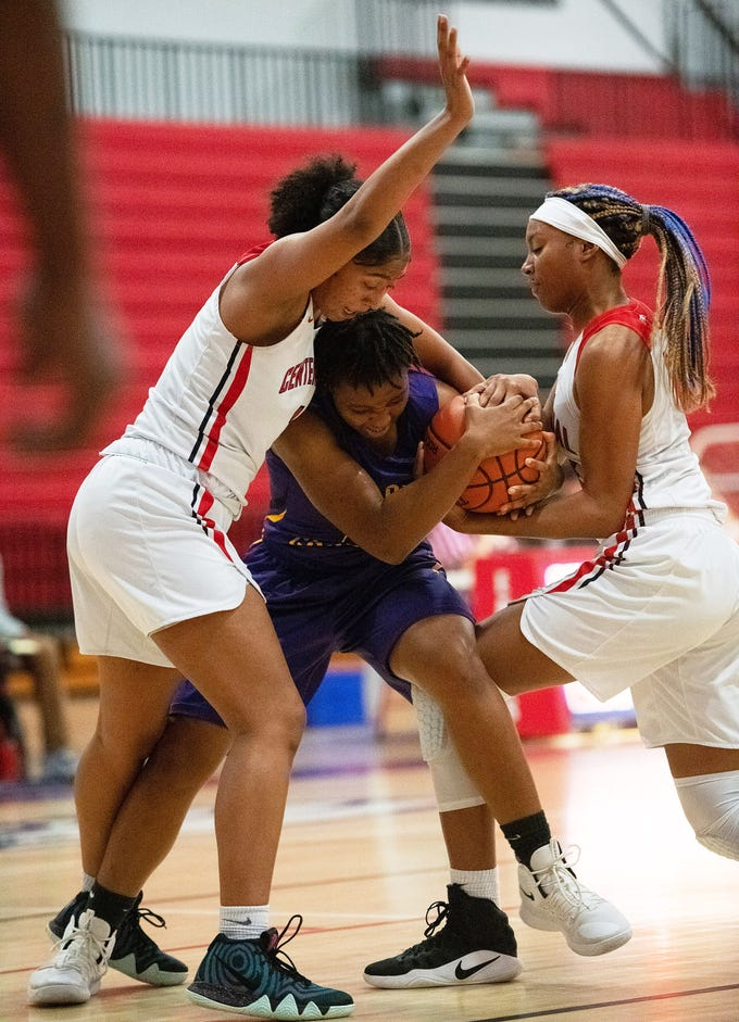 Fort Pierce Central's Amaya Howard (center) battles for possession of the ball against Centennial's Jannae Leon (left) and Raven Evans (right) in the first half their game at Centennial High School on Friday, January 25, 2019 in Port St. Lucie.