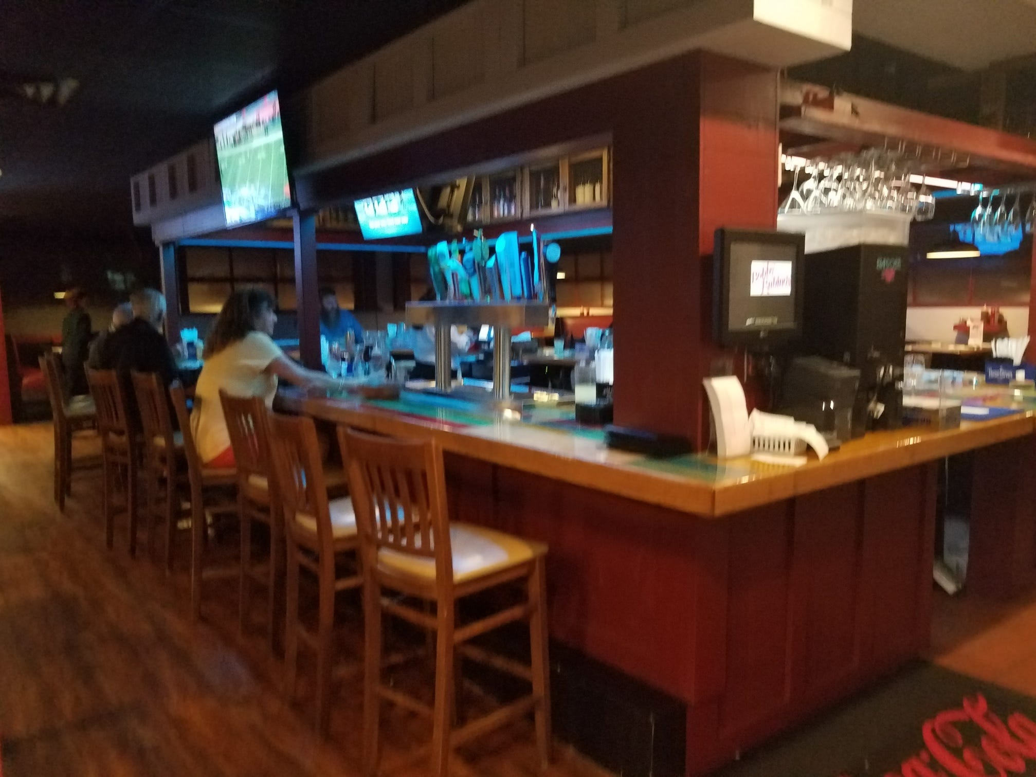 The interior of Bobby Rubino's is cozy with dark wood. There is both table and booth seating, along with a separate bar area.