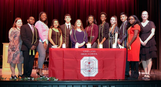 (From left) April Marchesano-Hemminger, advisor; Isaac Garrett, parliamentarian; Evin Guilford, historian; Sakshi Thakkar, corresponding secretary; Igor Shanava, co-vice president; Sofia Babenko, co-president; Nyah Marshall, co-president; Simileoluwa Adenugba, co-vice president; Carly Mayhew, recording secretary; Francis Virtucio, liaison; Natalie Garrett, treasurer; and Donna Garrett, advisor, are pictured at Vineland High School's National Honor Society induction ceremony.