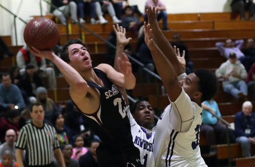Scarsdale's Cole Kattan (23) puts up a shot in front of New Rochelle's Jaheim Jones (31) during boys basketball action at  New Rochelle High School Jan. 25, 2019. Scarsdale won the game in overtime 48-46.