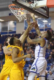Delaware's Eric Carter (right) scores against Drexel's Alihan Demir (left) and Tim Perry, Jr. in the Blue Hens' 76-75 win at the Bob Carpenter Center Saturday.