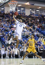 Delaware's Ithiel Horton moves for a dunk as Drexel's Camren Wynter trails in the second half of the Blue Hens' 76-75 win at the Bob Carpenter Center Saturday.