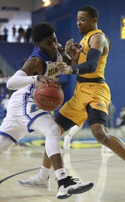 Delaware's Ryan Allen (left) is fouled by Drexel's Troy Harper in the first half of the Blue Hens' 76-75 win at the Bob Carpenter Center Saturday.