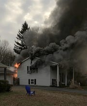 Smoke and flames shoot from a home on Oakfield Drive in the Scottfield neighborhood near Newark Saturday.