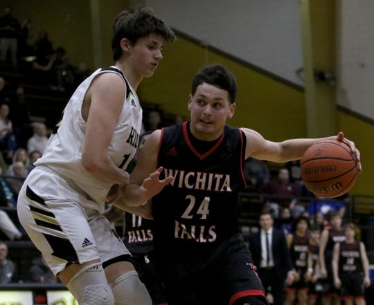 Wichita Falls High School's Kobe Graham drives to the basket by Rider's Ty Caswell Friday, Jan. 25, 2019, at Rider.
