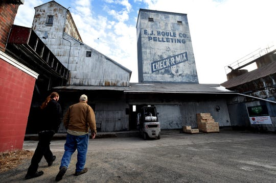 Alexander Brand, left, and James Houle walk to the warehouse at Houle's Feed Mill in Forest Lake, Minn. on Thursday, Jan. 10, 2019. The business, started as a feed mill by E.J. Houle in 1916, is for sale. A development company wants to buy Houle's and replace it with a 100-room hotel and convention center.