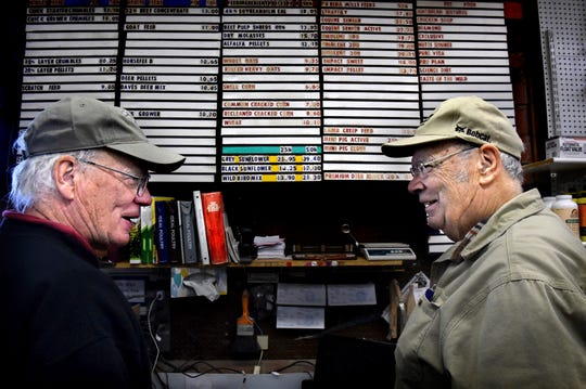 Brothers Gary Houle, left, and James Houle talk in front of the price board at Houle's Feed Mill in Forest Lake, Minn. on Thursday, Jan. 10, 2019. For 103 years, the business has been selling feed and chickens and horse equipment. Now, the owners of the family-owned business, who are all in their 70s, are ready to retire.