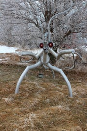 In this Jan. 13, 2019 a praying mantis sculpture is displayed near Martin Freed's home in Loomis, Neb. Spiders, the praying mantis and other bugs are scattered along a half-mile stretch of road in Loomis. While the giant insects may appear to be characters in a science fiction movie upon first glance, they are the creation of Freed.