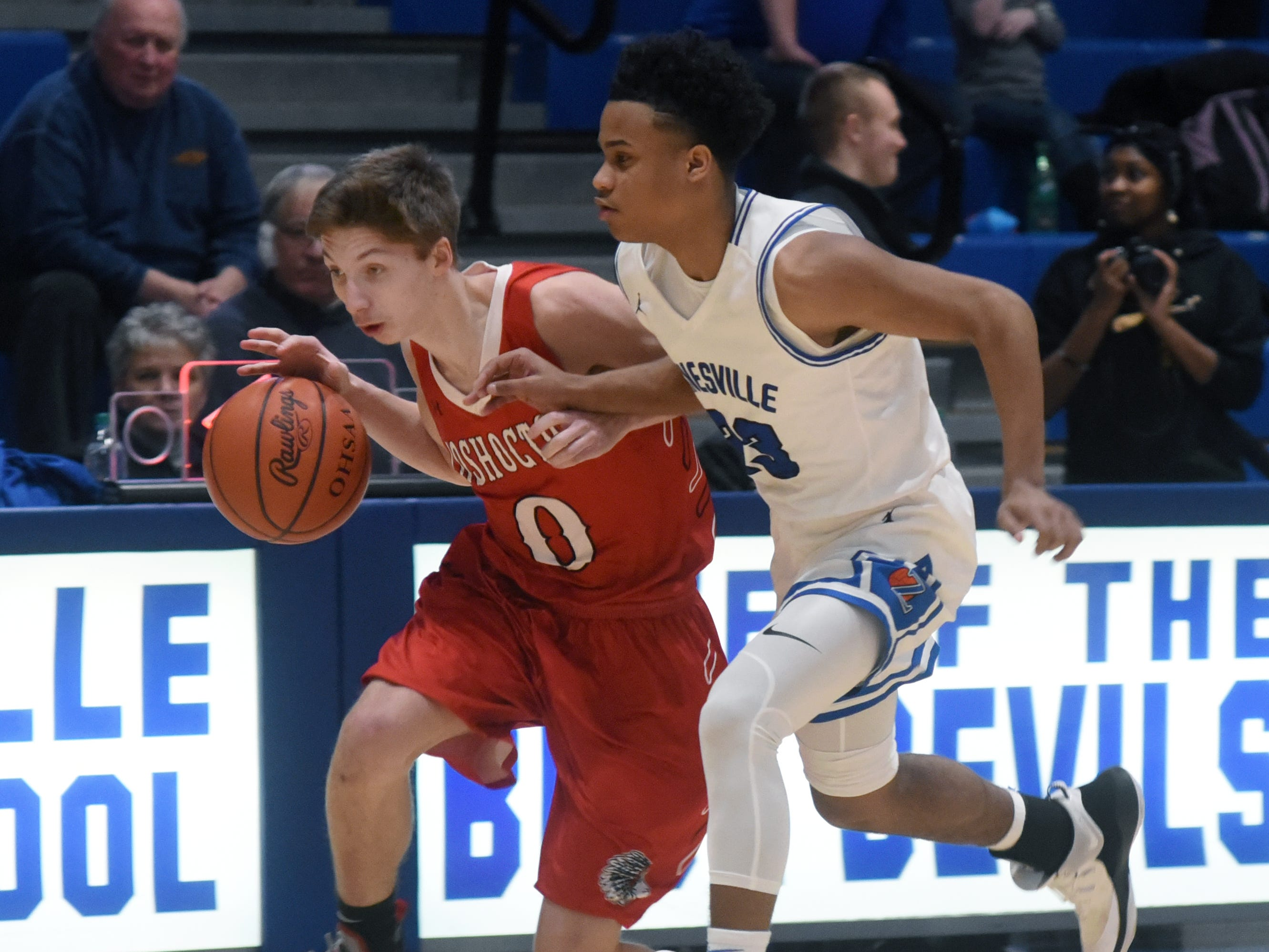 Gaven Williams, of Coshocton, drives up court against Zanesville's Greg Gibson.
