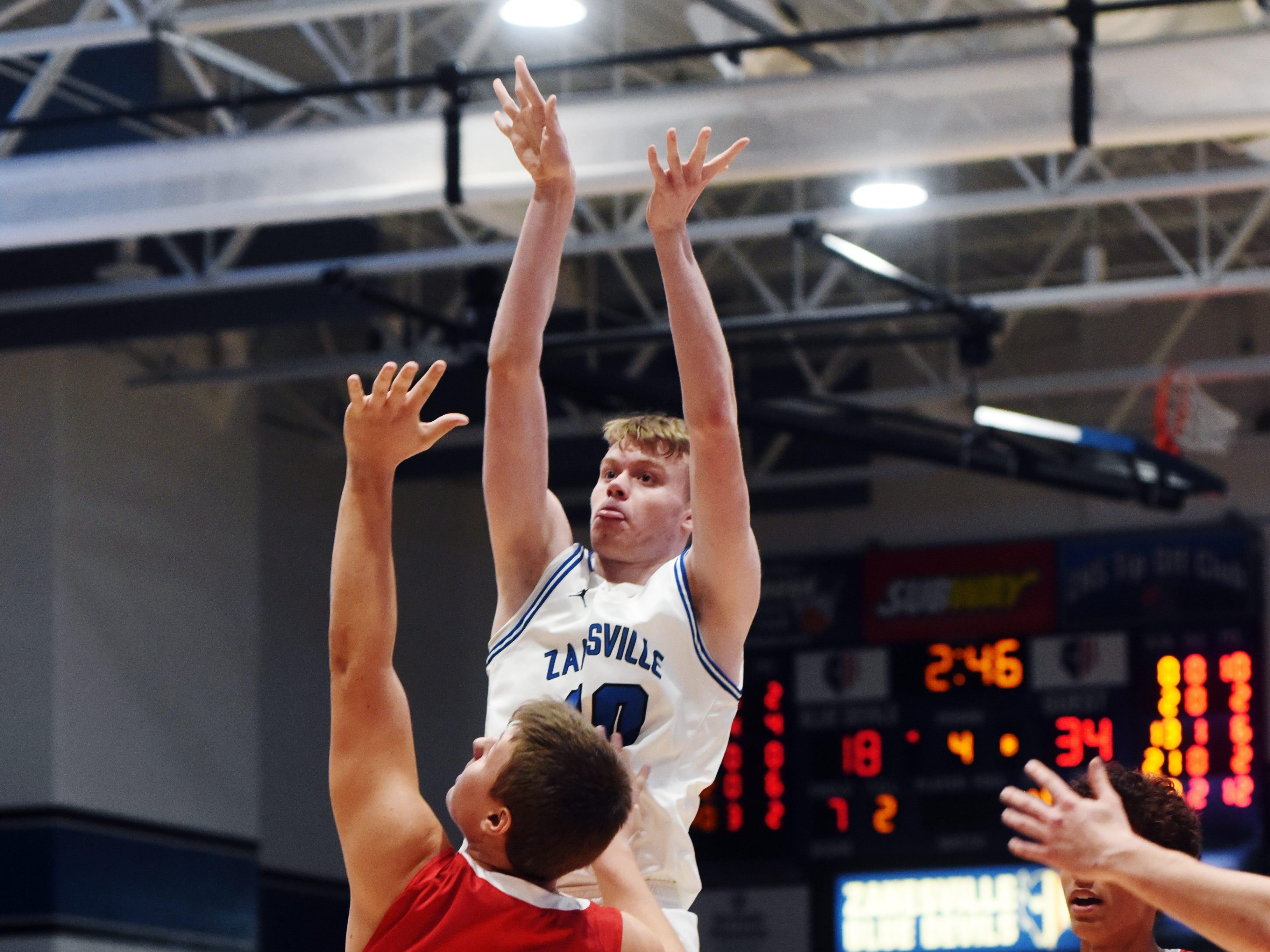 Brennan Reasoner shoots a jumper over Logan Desnder in Zanesville's 38-27 loss to visiting Coshocton on Friday night at Winland Memorial Gymnasium.