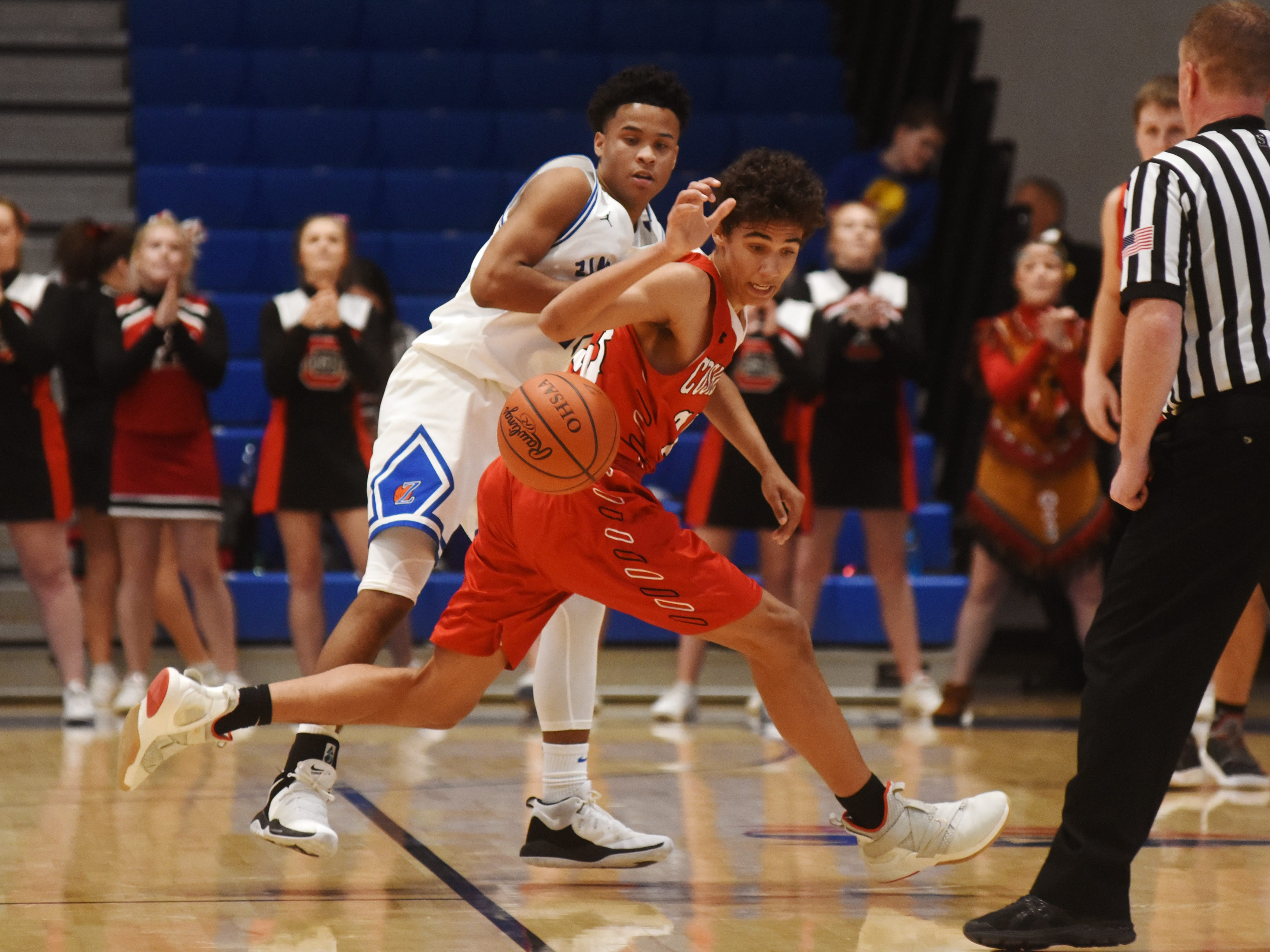 Zanesville's Greg Gibson, left, and Coshocton's Tyren Walker go after a loose ball.