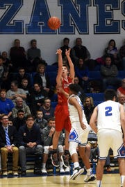 Gaven Williams shoots a 3-pointer over Cory Norris during Coshocton's 38-27 win against Zanesville on Friday night at Winland Memorial Gymnasium.
