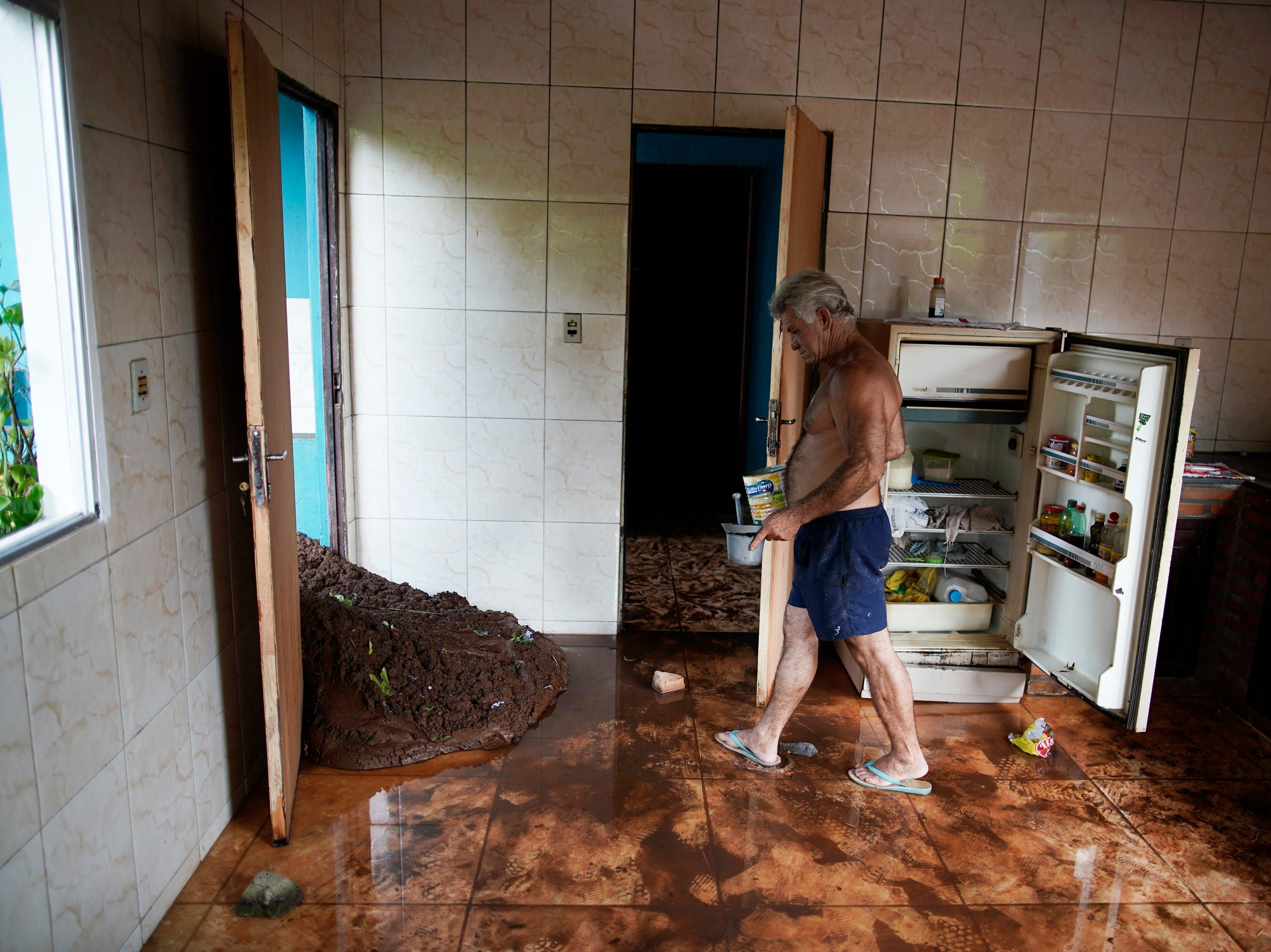 Darcy Brum walks past mud that entered in the kitchen of the house of his father-in-law near Brumadinho, Brazil, Saturday, Jan. 26, 2019. The dam that held back mining waste collapsed, inundating a nearby community in reddish-brown sludge, killing several people and leaving scores of others missing.