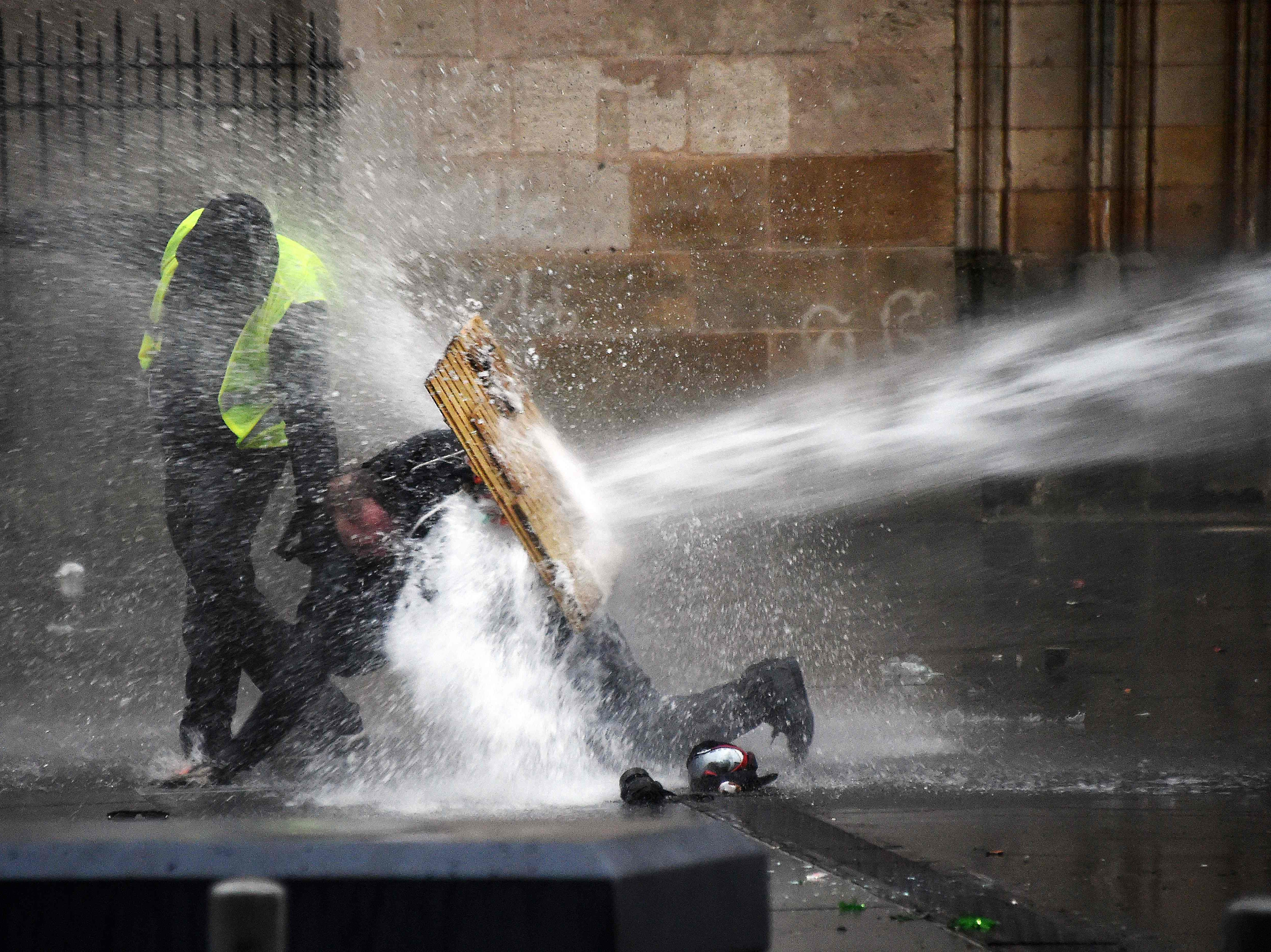 "Protesters protect themselves from water cannon during an anti-government demonstration called by the Yellow Vests ""Gilets Jaunes"" movement on Jan. 26, 2019 in Bordeaux."
