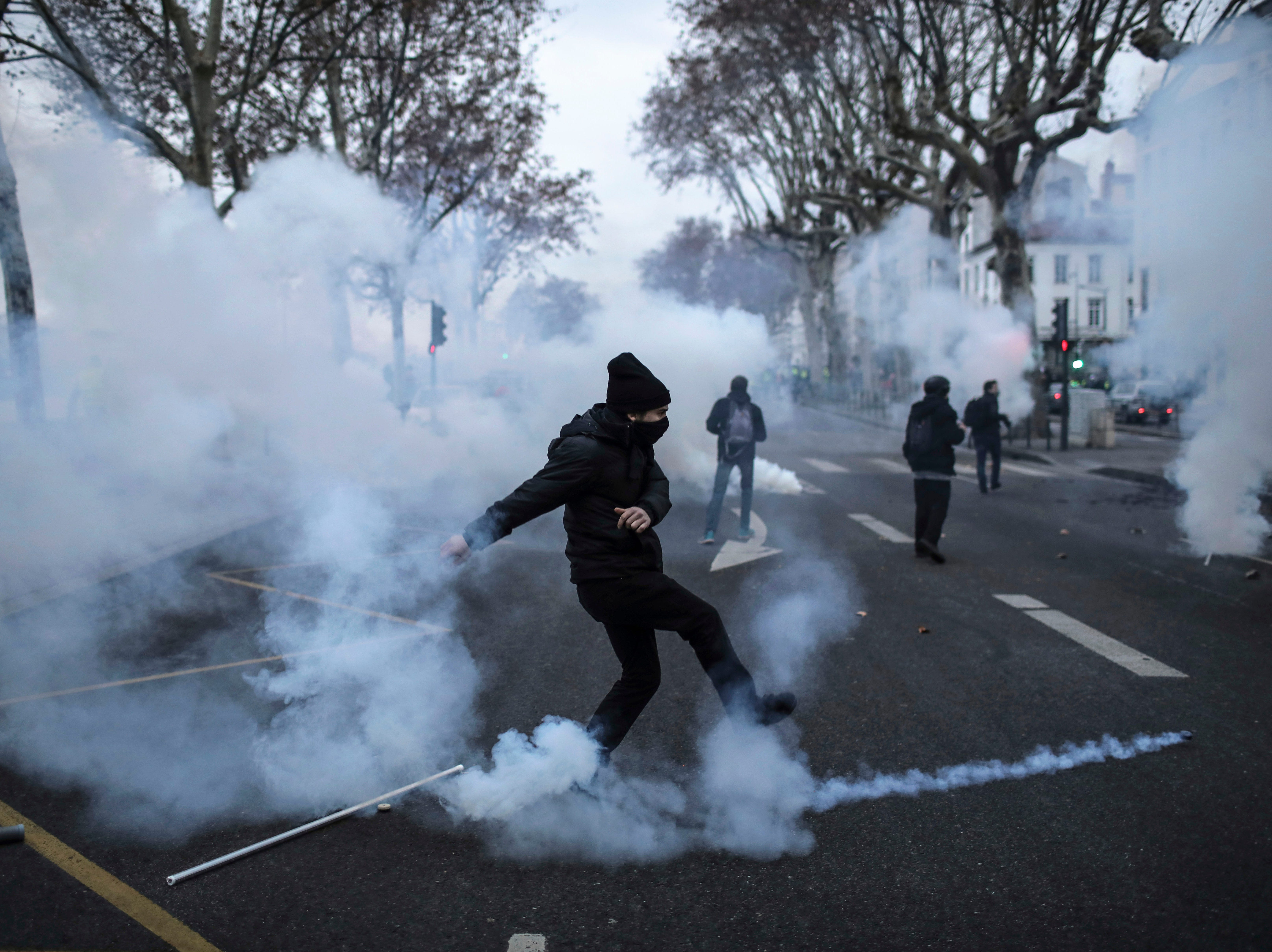 A yellow vest demonstrator kicks away a teargas canister during clashes in Lyon, central France, Saturday, Jan. 26, 2019. Fights broke out as the movement kept up pressure on President Emmanuel Macron despite internal divisions and growing worries about protest violence.