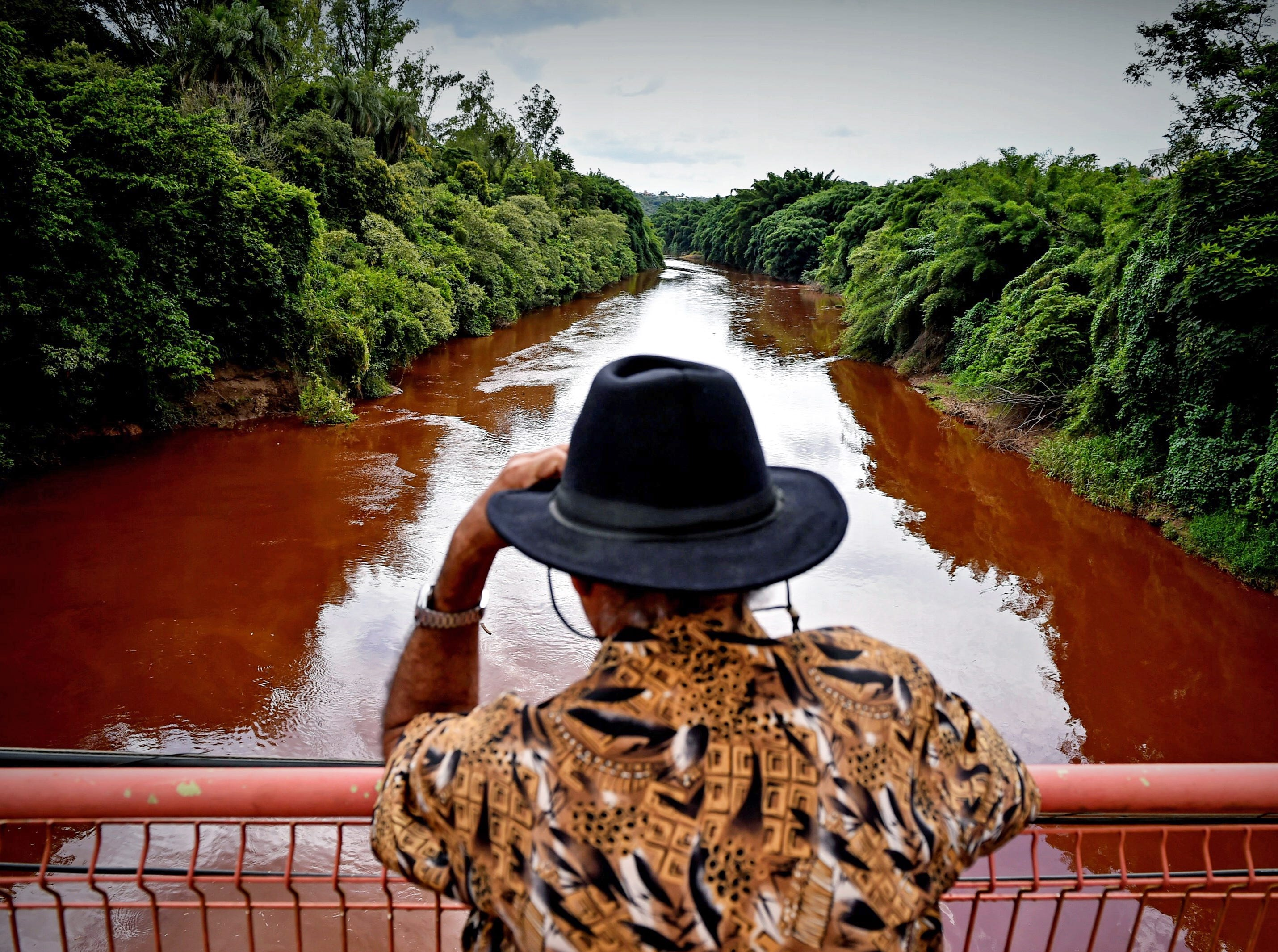 A man watches the Paraopeba River with mud and waste from the disaster caused by dam spill in Brumadinho, Minas Gerais, Brazil on Jan. 26, 2019.