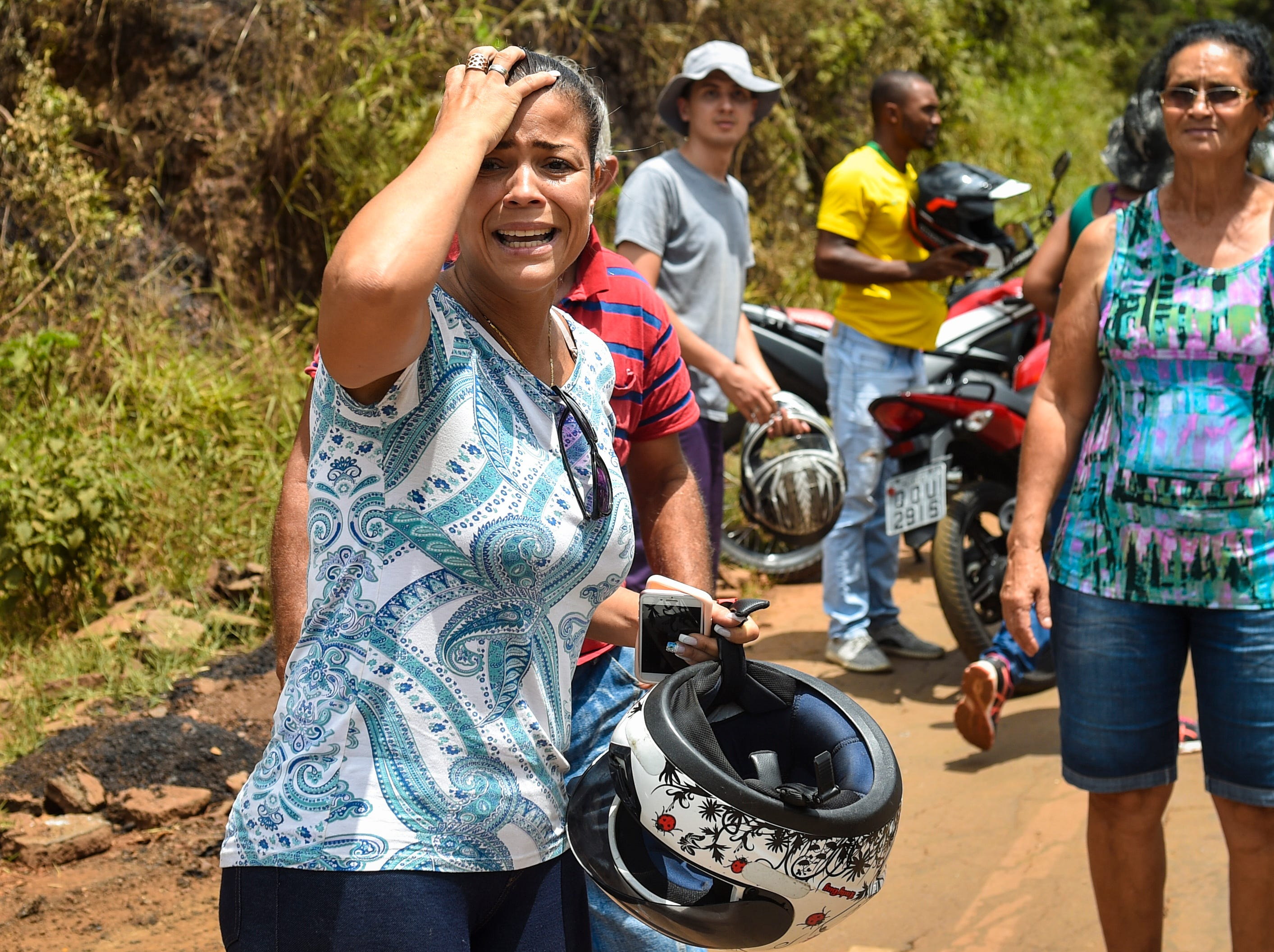 A woman cries as she sees the damages caused by the mining waste a day after the collapse of a dam from an iron-ore mine belonging to Brazil's mining company Vale in Brumadinho on Jan. 26, 2019. It has been reported that at least nine people were killed and around 300 more are missing.
