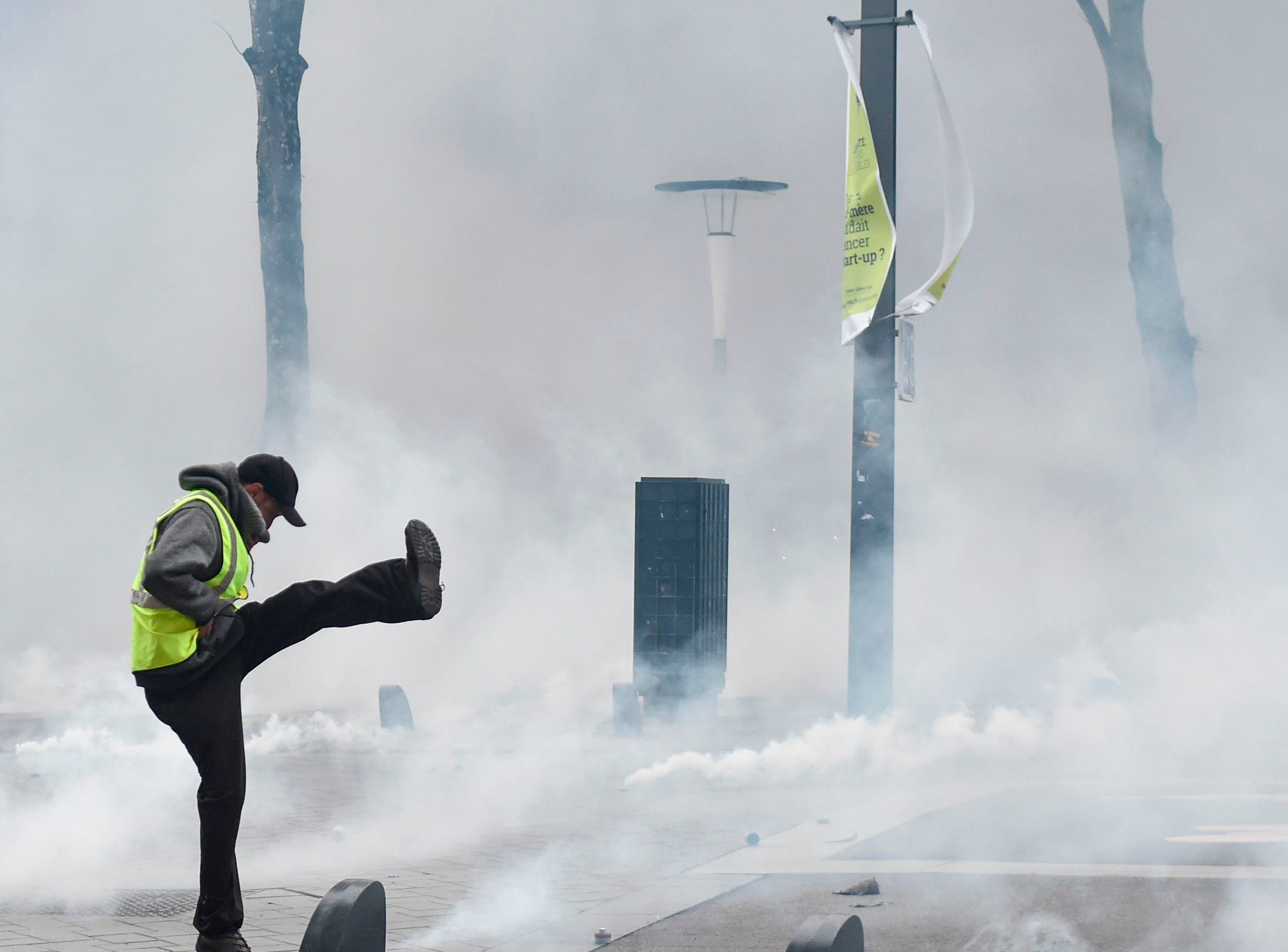 "A protester throws back a tear gas canister during an anti-government demonstration called by the Yellow Vests ""Gilets Jaunes"" movement in Nantes, western France, on Jan. 26, 2019."