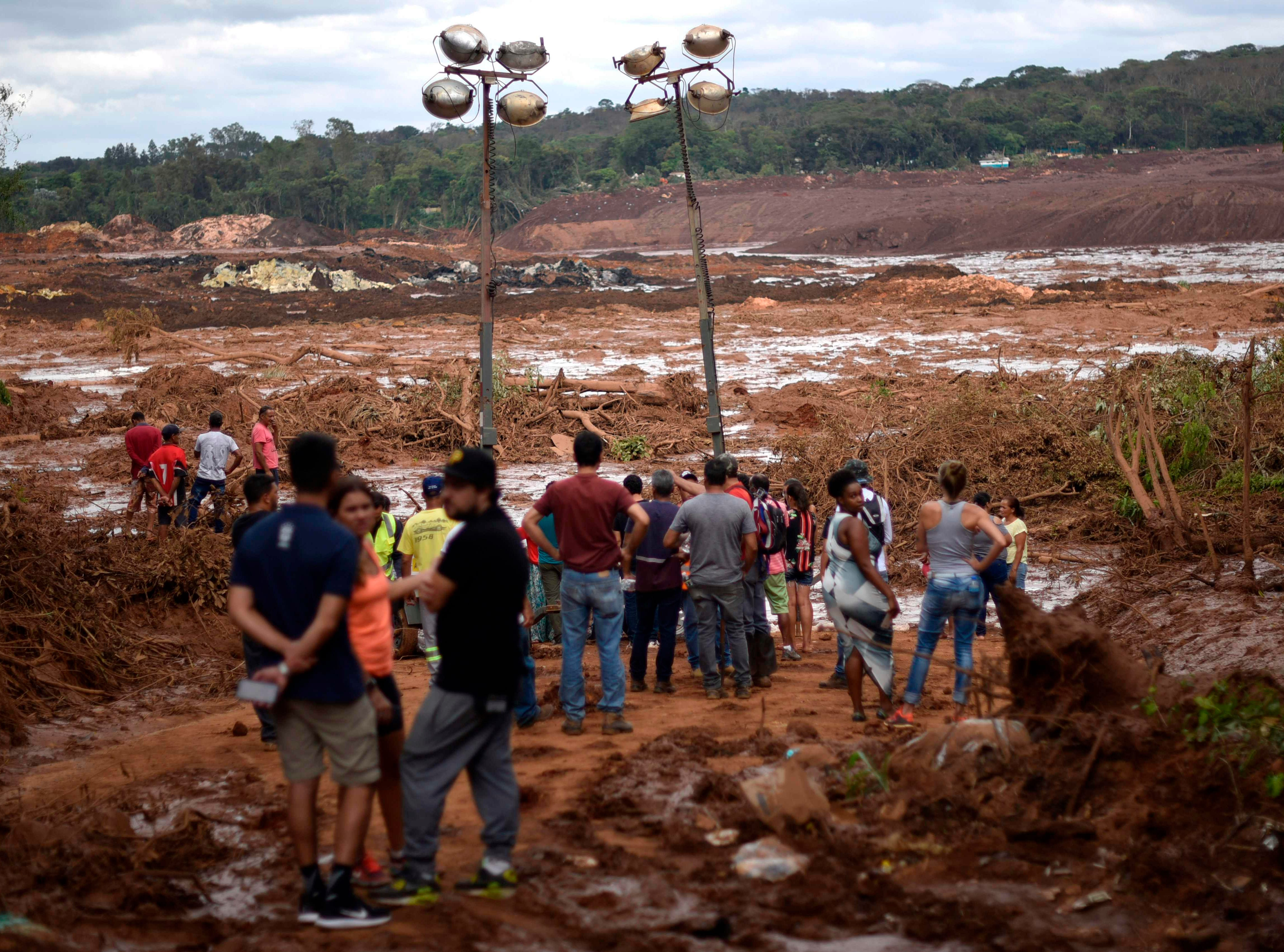 People look at the damage after the collapse of a dam that belonged to Brazil's giant mining company Vale, near the town of Brumadinho in southeastern Brazil, on Jan. 26, 2019.