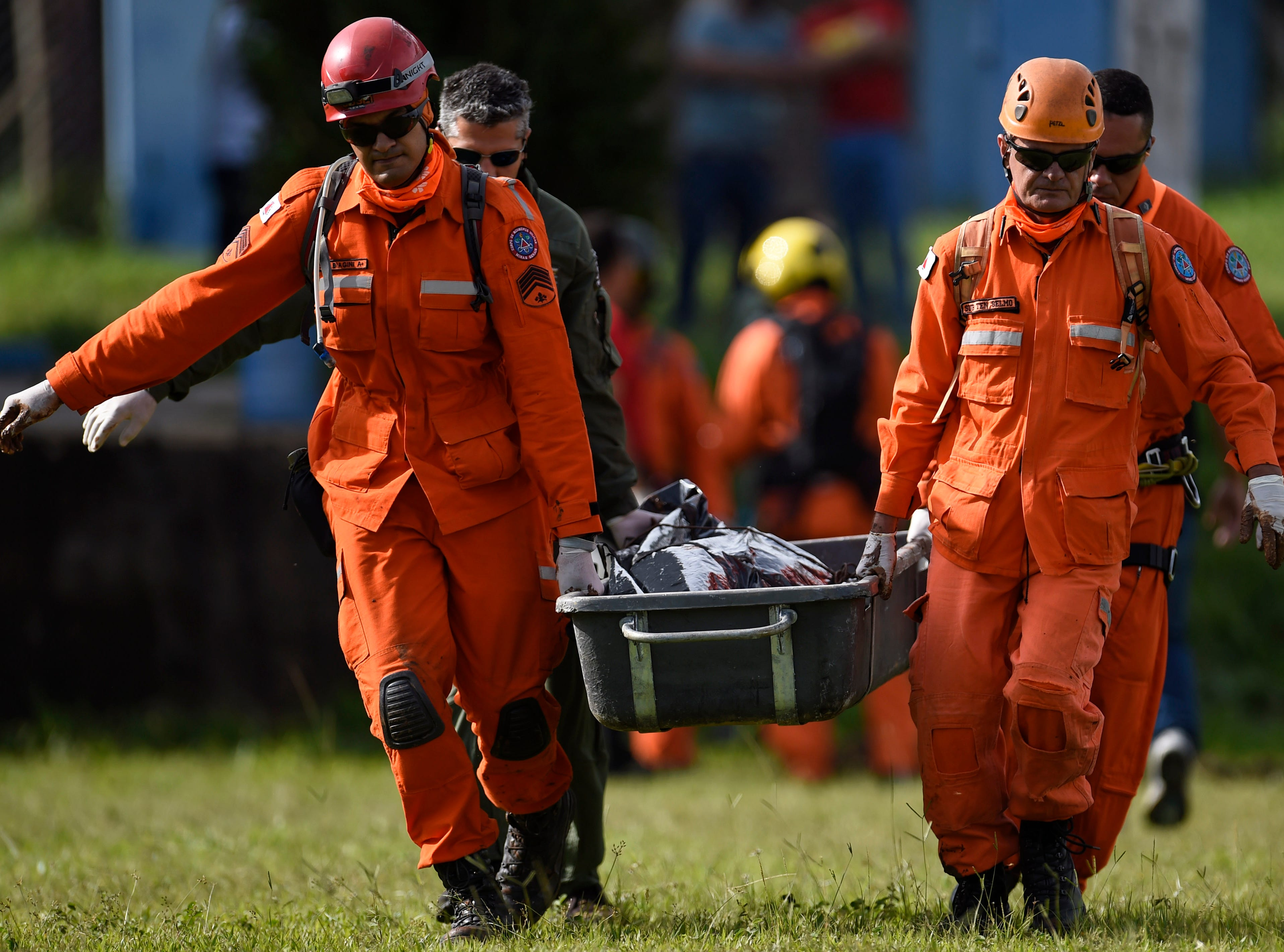 Military firefighters carry the corpse of a victim recovered from the mud a day after the collapse of a dam at an iron-ore mine belonging to Brazil's giant mining company Vale, near the town of Brumadinho in the state of Minas Gerias in southeastern Brazil, on Jan. 26, 2019.