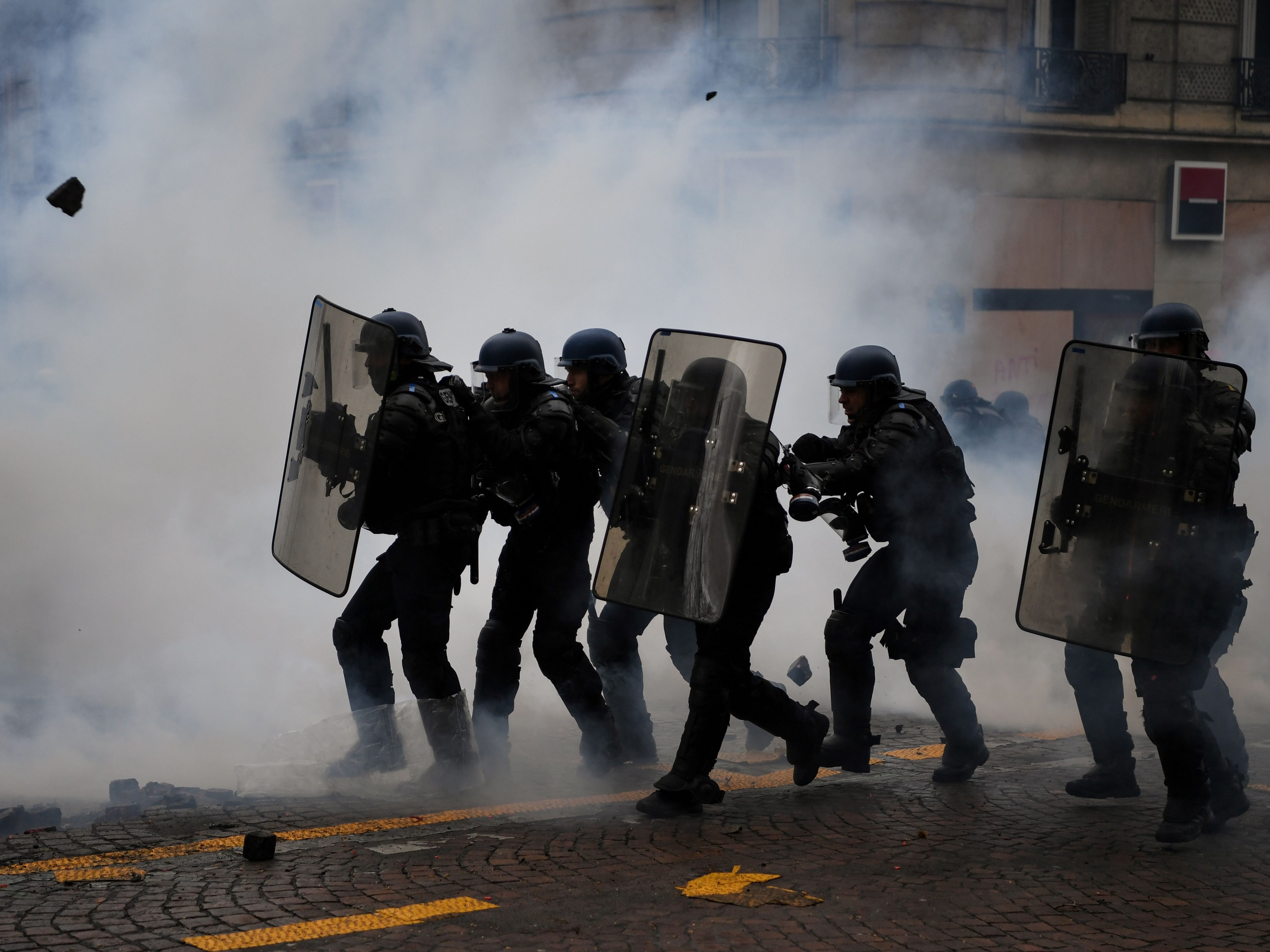 "Riot police officers clash amid smoke with protesters during an anti-government demonstration called by the Yellow Vests ""Gilets Jaunes"" movement on Jan. 26, 2019.  'Yellow vest' anti-government protesters have taken to the streets in France for the 11th consecutive Saturday on January 26, despite recent divisions in their ranks, and with a displayed tenacity facing an executive which is regaining popularity ten days after the opening of the ""great national debate"", the French president's bid to prove he will take on board the fierce criticism of ""yellow vest"" protesters who have upended his reform agenda."