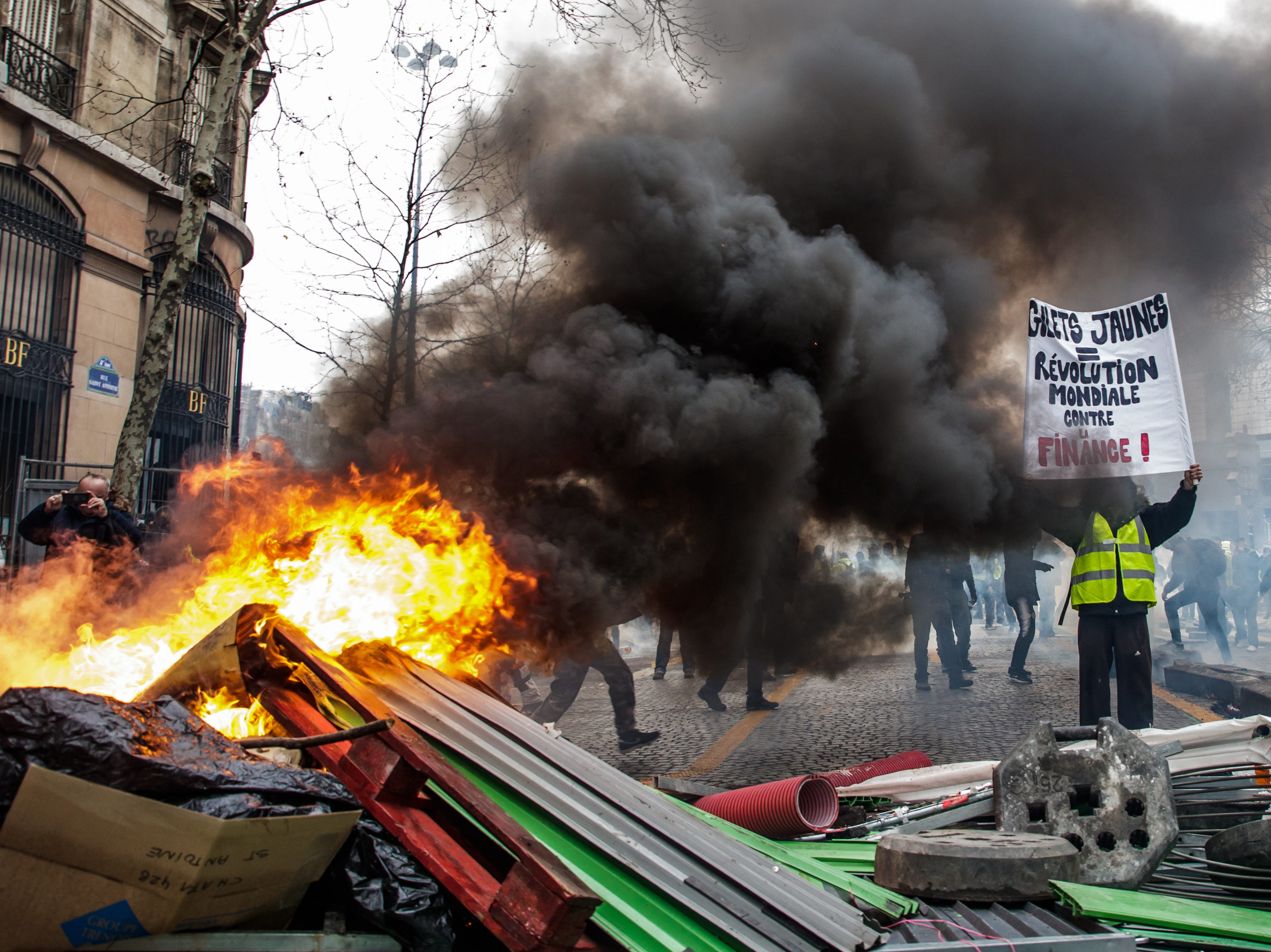 A protester from the 'Gilets Jaunes' (Yellow Vests) movement holds a poster reading 'Yellow Vests World Revolution against the Finance' as clashes erupt next to the Place de la Bastille during the 'Act XI' demonstration (the 11th consecutive national protest on a Saturday) in Paris, France on Jan. 26, 2019.