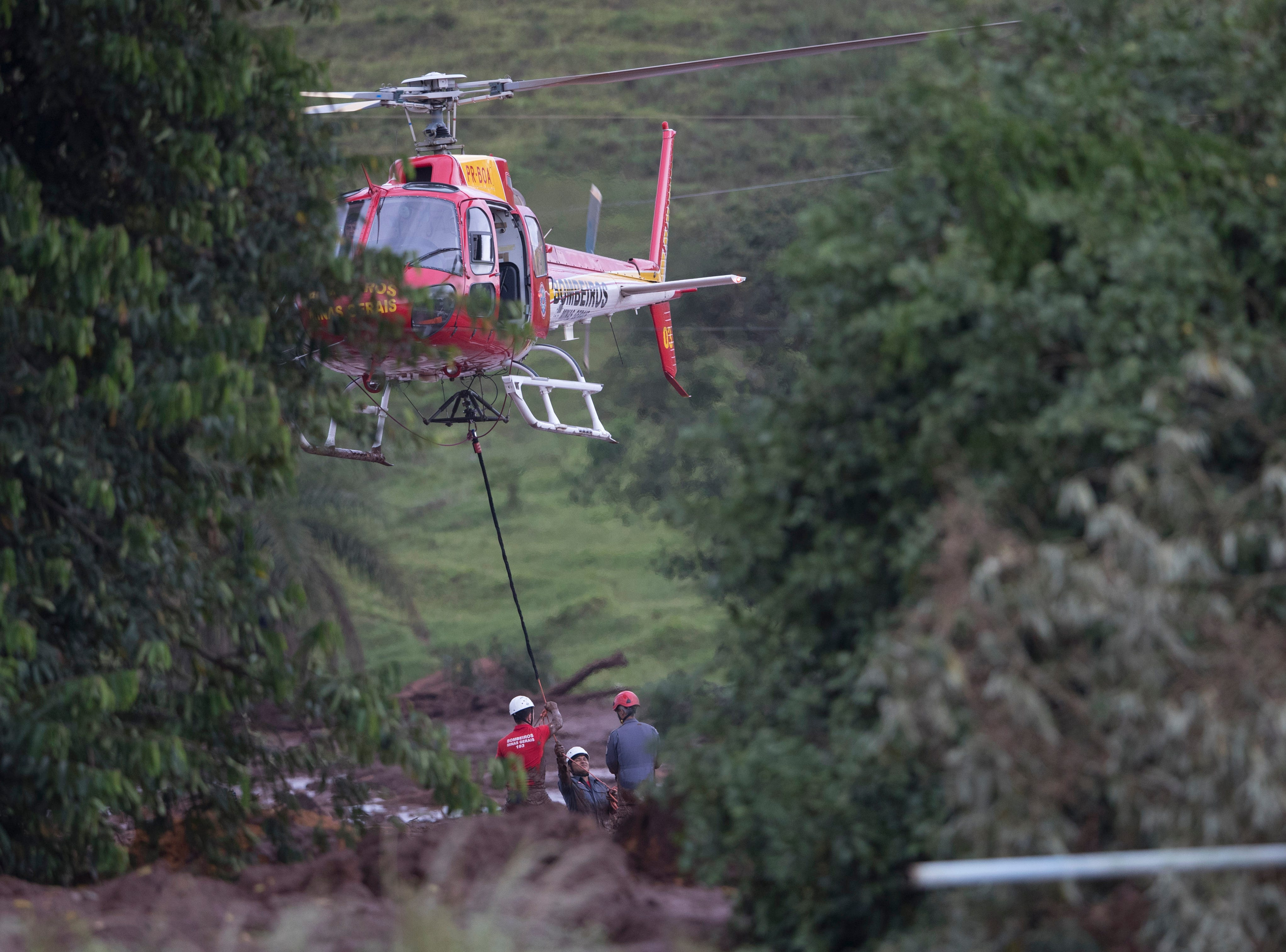 Firefighters prepare to lift, with a helicopter, a body rescued from the mud, after a dam collapse near Brumadinho, Brazil, Saturday, Jan. 26, 2019.