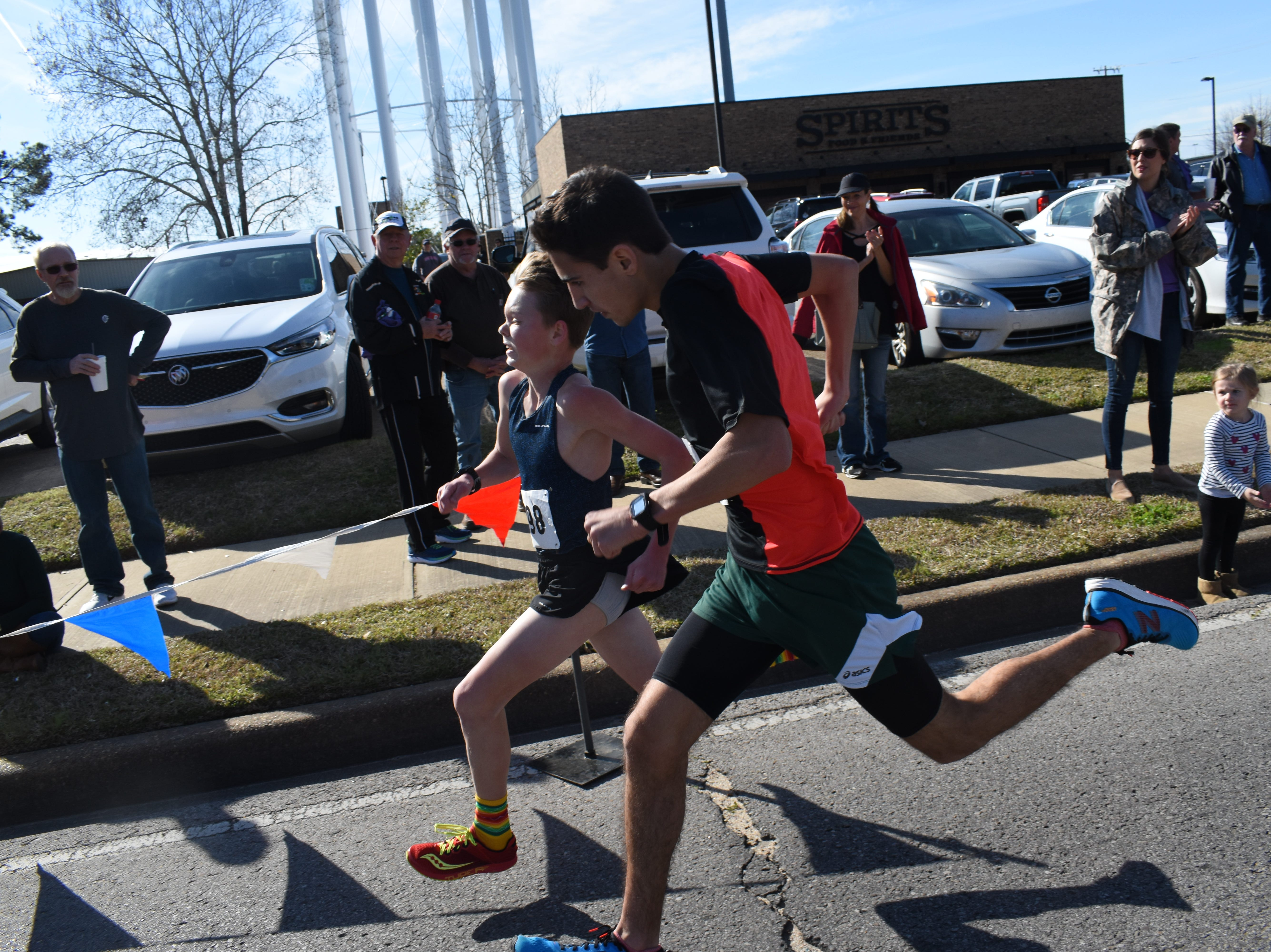 Charles Beard,13, (far left) edges out Braden Scalisi, 16, to come in third in the Spirits 5K with a time of 18:24.4. Scalisi placed fourth with 18:24.6.Over 212 runners participated in the 19th annual Spirits 5K and 1-mile Fun Run benefitting the Manna House Saturday, Jan. 26, 2019. About 75 runners participated in a new event held this year - the Beer Run. Runners had to drink four beers and sprint to the finish line. Proceeds from the runs benefit the Manna House which serves free meals year round to anyone who needs a meal regardless of income. Over 200 people a day are fed. The Manna House opened in 1990 and was the vision of Father Gerad Foley.