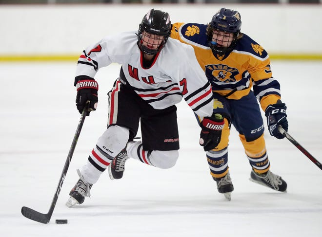 Ethan Long, left, of Neenah/Hortonville/Menasha carries the puck into the offensive zone against Wausau West during a game earlier this season in Ashwaubenon.