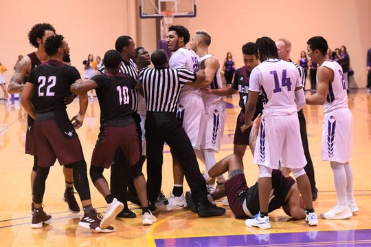 Hardin-Simmons and McMurry players have to be separated by the officials after a jump ball at the Mabee Complex on Saturday, Jan. 26, 2019. The War Hawks won 75-70.